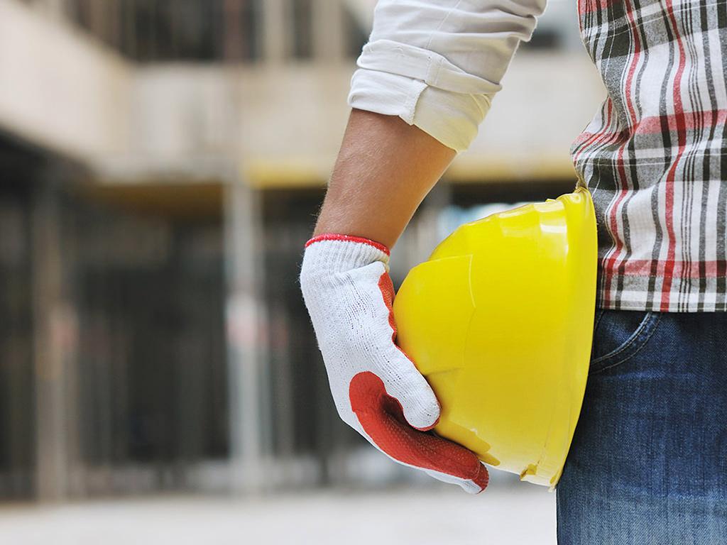 Lavoratore tiene in mano un casco di sicurezza